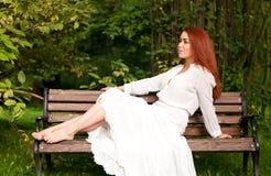 Kvinna som sitter på bänk arkivfoton
