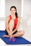 Kvinna som sitter på den matta övningen royaltyfria bilder
