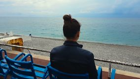Kvinna som sitter på den tomma strandsjösidan som kopplar av på semester, ensamhet, sorgsenhet stock video
