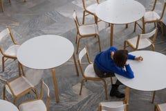 Kvinna som sitter på den vita tabellen Top beskådar arkivfoton