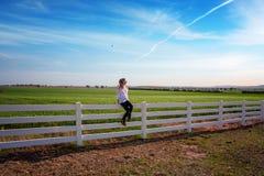 Kvinna som sitter på det vita lantgårdstaketet i lantliga fält fotografering för bildbyråer