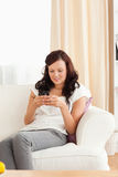Kvinna som sitter på en sofa som texting Royaltyfria Foton