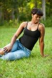 Kvinna som sitter på gräset Arkivfoto
