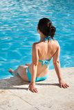 Kvinna som sitter på kanten av simbassängen Royaltyfria Foton