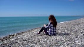Kvinna som sitter på Pebble Beach och ser till havet arkivfilmer