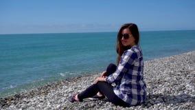 Kvinna som sitter på Pebble Beach, posera som ser till kameran stock video