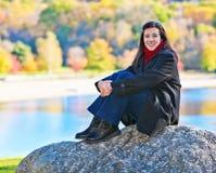 Kvinna som sitter på rock arkivfoto