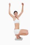 Kvinna som sitter på scales, medan lyfta henne armar Arkivbild