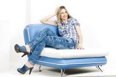 Kvinna som sitter på sofaen Royaltyfria Foton