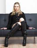 Kvinna som sitter på sofaen Royaltyfria Bilder