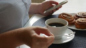 Kvinna som sitter på tabellen och att dricka kaffe med kanelbruna bullar, stiring kaffe och att se smartphonen lager videofilmer