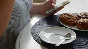 Kvinna som sitter på tabellen och att dricka kaffe med kanelbruna bullar, stiring kaffe och att se smartphonen stock video