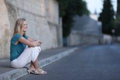 Kvinna som sitter på trottoaren Arkivfoton