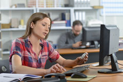 Kvinna som sitts på skrivbordet royaltyfri fotografi