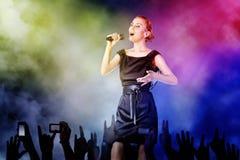 Kvinna som sjunger för henne ventilatorer på en konsert Royaltyfri Foto