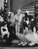 Kvinna som sjunger med barn på trappuppgång på jul (alla visade personer inte är längre uppehälle, och inget gods finns leverantö Royaltyfria Foton