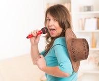 Kvinna som sjunger med en mikrofon Arkivbild
