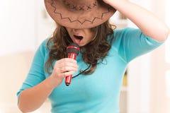 Kvinna som sjunger med en mikrofon Fotografering för Bildbyråer