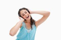 Kvinna som sjunger, medan lyssna till musik Arkivbild