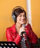 Kvinna som sjunger, medan se bort i inspelningstudio royaltyfri foto