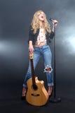Kvinna som sjunger på etapp med Mic och gitarren Arkivbild