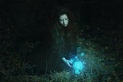 Kvinna som skördar den magiska blomman i skogen arkivbilder