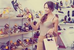 Kvinna som sköter par av skor Royaltyfria Bilder