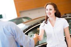 Kvinna som skakar händer med bilförsäljaren Arkivfoto