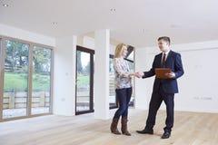 Kvinna som skakar händer med fastighetsmäklaren In New Home Arkivfoton