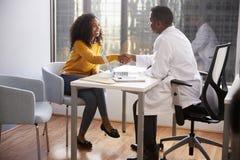 Kvinna som skakar händer med manlig konsultation för doktor In Hospital Office royaltyfria foton