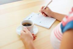 Kvinna som skissar och dricker kaffe arkivfoto