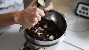 Kvinna som skivar kakaosmör för att laga mat hem- gjord choklad stock video