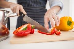 Kvinna som skivar upp röd peppar Arkivbild
