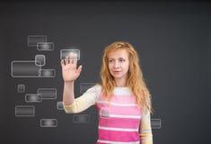 Kvinna som skjuter en knapp på en pekskärmmanöverenhet Arkivbild