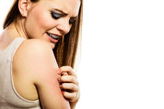 Kvinna som skrapar hennes arm Arkivfoto