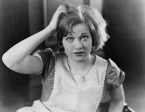 Kvinna som skrapar hennes huvud (alla visade personer inte är längre uppehälle, och inget gods finns Leverantörgarantier att det  arkivbild