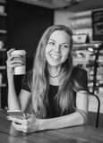 Kvinna som skrattar den hållande koppen kaffe som är svartvit royaltyfria bilder