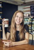 Kvinna som skrattar rymma en kopp kaffe royaltyfria foton