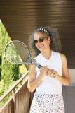 Kvinna som skrattar tennisracket och tennisklänningen royaltyfria foton