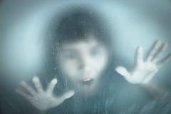 Kvinna som skriker bak nedfläckat eller smutsigt fönsterexponeringsglas Arkivfoto