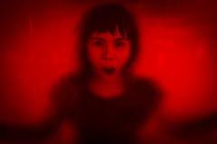 Kvinna som skriker bak nedfläckat eller smutsigt fönsterexponeringsglas Arkivbild