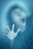 Kvinna som skriker bak nedfläckat eller smutsigt fönsterexponeringsglas Royaltyfri Foto