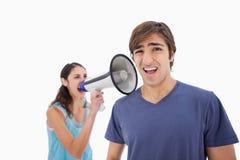 Kvinna som skriker på henne pojkvännen till och med en megafon Arkivbilder