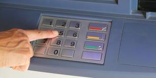 kvinna som skriver den hemliga koden på ATM-tangentbordet Arkivfoton