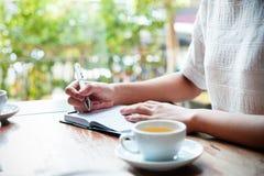 Kvinna som skriver en dagbok Arkivfoto