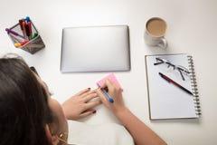 Kvinna som skriver en klibbig anmärkningspåminnelse Arkivbild