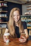 Kvinna som skriver ett meddelande i mobiltelefonen och dricker kaffe arkivbild