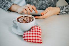 Kvinna som skriver ett meddelande till hennes valentin som väntar på kafét valenti Arkivfoto