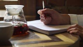 Kvinna som skriver något i anteckningsbok i ett kafé stock video