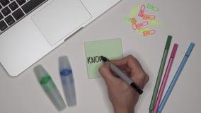 Kvinna som skriver upp kunskap på notepaden, slut Bärbar dator och brevpapper på skrivbordet lager videofilmer